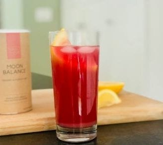 moon balance superfood mix lemonade in glass with lemons on cutting board and mix container-your super superfood reviews-mealfinds