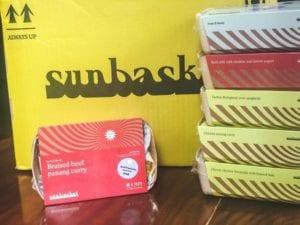 sunbasket oven ready meals stacked up in front of box-sunbasket reviews-mealfinds