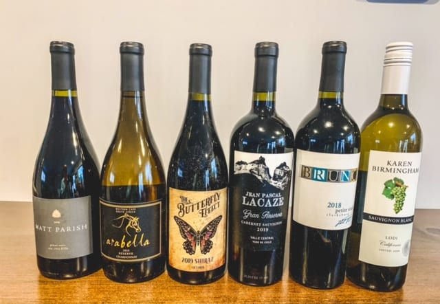 six wine bottles side by side on table-naked wines reviews-mealfinds