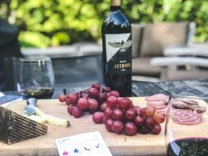 cheese grapes meat board with wine bottle and glasses-bright cellars review-mealfinds