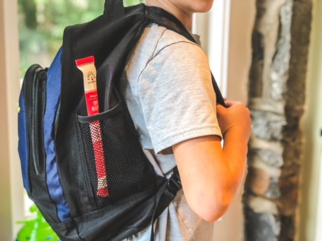 kid with backpack with meat stick in pocket-firecreek snacks snack sticks review-mealfinds