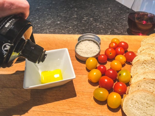 manni olive oil poured into bowl with bread and tomatos-manni best olive oil revews-mealfinds